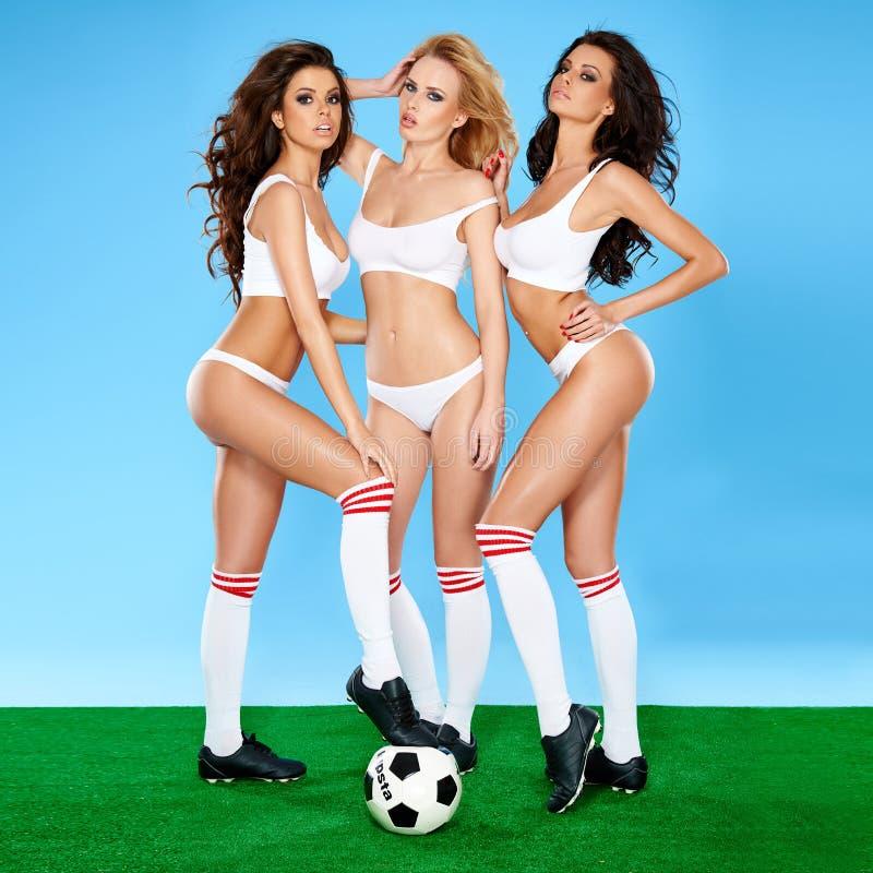 三位美丽的性感的女子足球运动员 库存照片