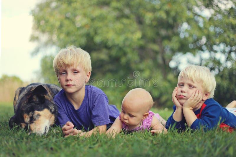三使幼儿和狗松弛外部不耐烦 免版税库存照片