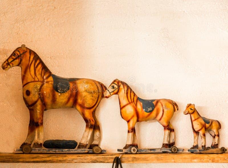 三匹老玩具马,在一个木架子 免版税库存图片