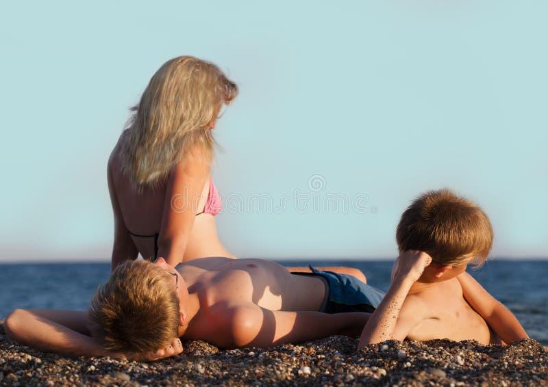 三十几岁坐海滩 免版税库存图片