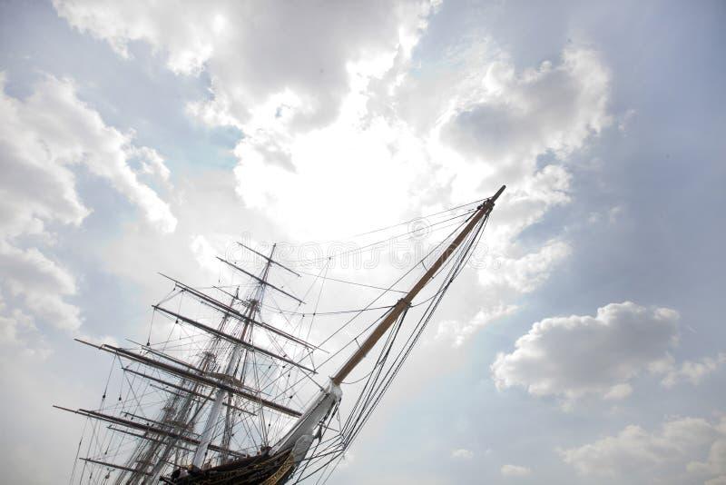 三反对多云天空的被上船桅的船低角度视图  免版税库存照片
