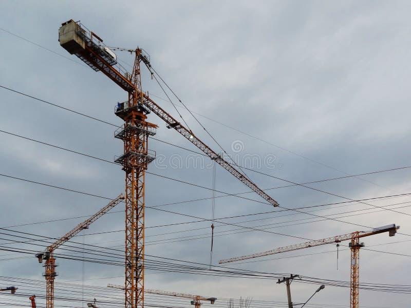 三反对蓝天的黄色建筑用起重机 图库摄影