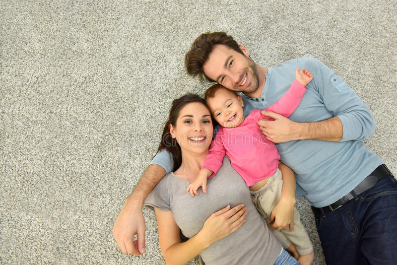三口之家上部看法放置在地毯地板的 免版税库存照片