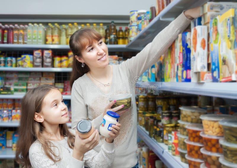 三口之家在商店的购买的食物 免版税库存图片