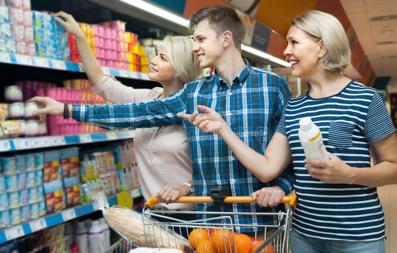 三口之家成人选择酸奶 免版税库存图片