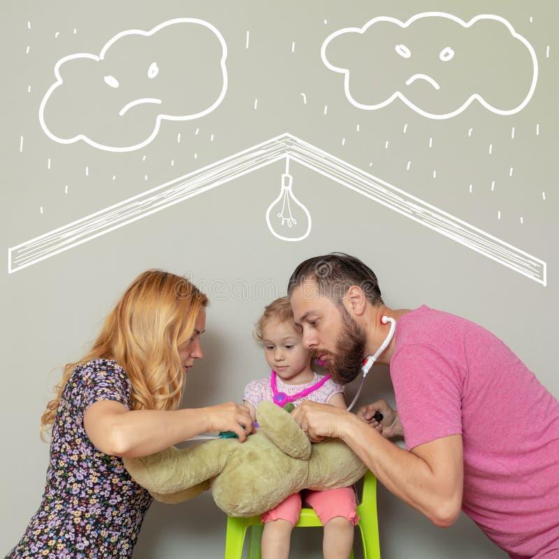 三口之家有玩具熊的使用的医生 爱的保护一个通过医疗保险金或家庭保险概念 库存图片