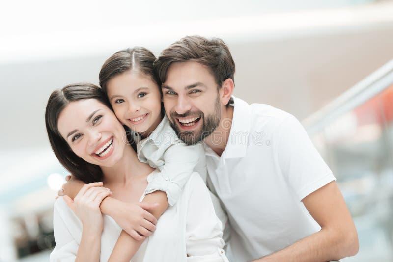 三口之家,父亲、母亲和女儿在购物中心 免版税图库摄影