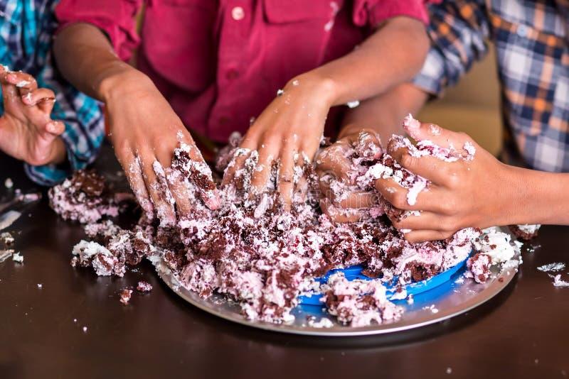 三只儿童的手捣毁蛋糕 免版税库存照片