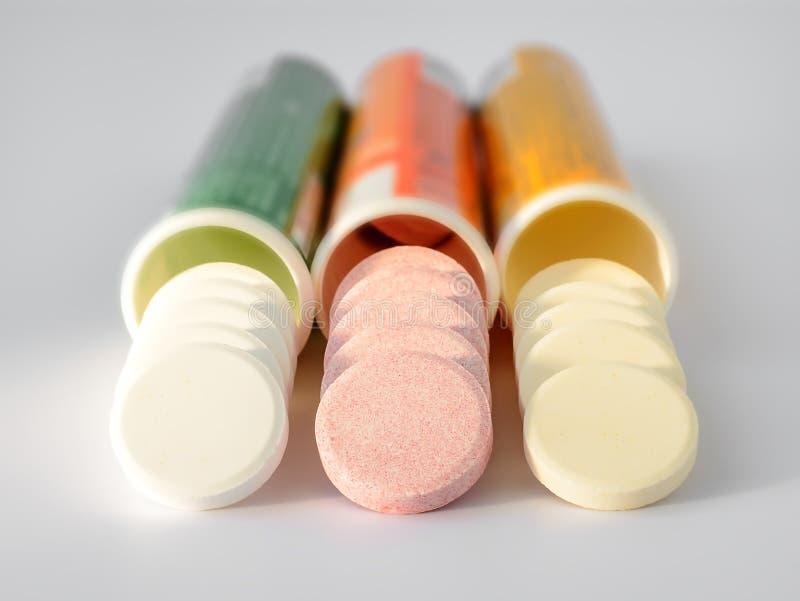 三可溶解冒泡维生素溢出在白色背景的塑料瓶外面 在阳光下 维生素和 库存照片