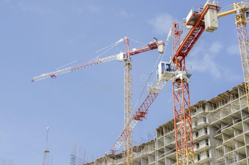 三台起重机箭头在一个水泥整体大厦上的建设中 免版税库存图片