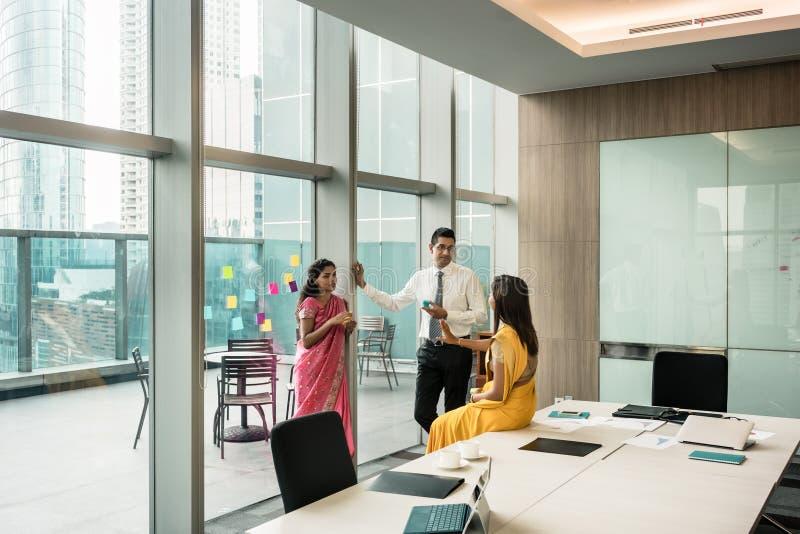 三名印地安雇员谈话在断裂期间在会议室 免版税库存照片