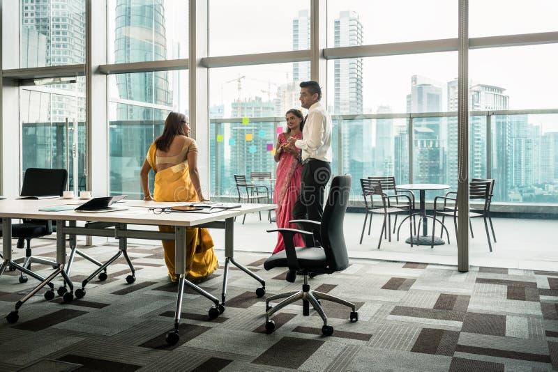 三名印地安雇员谈话在断裂期间在会议室 库存图片