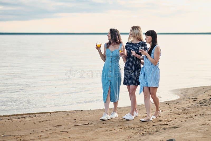 三名年轻可爱的妇女,蓝色礼服的沿海滨走 女朋友沟通,笑并且喝 库存图片