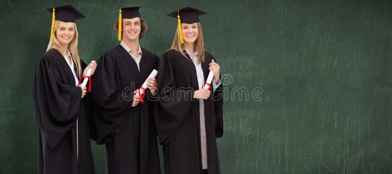 三名微笑的学生的综合图象拿着文凭的毕业生长袍的 免版税库存图片