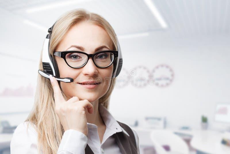 三名电话中心服务操作员在工作 画象微笑相当有耳机的女性帮助台雇员在工作场所 图库摄影