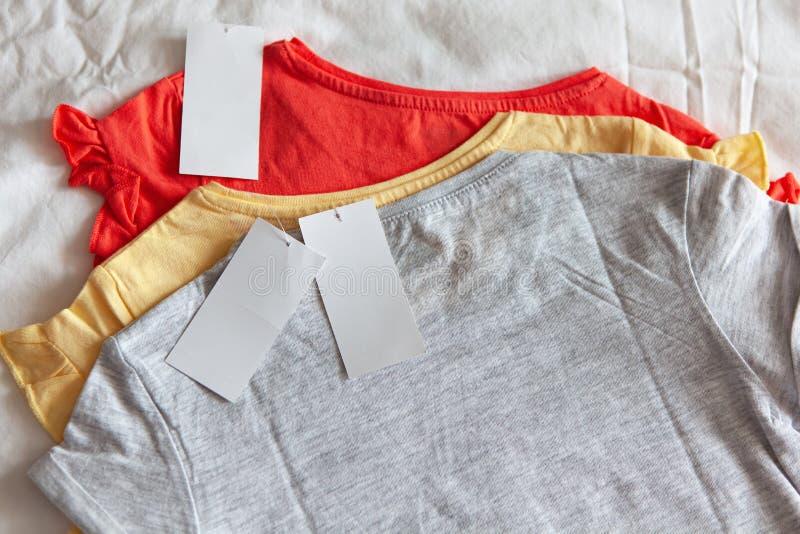 三在少量颜色的新的T恤杉与在白色背景的干净的标签 概念购物,夏天销售,折扣,有机棉花 库存照片