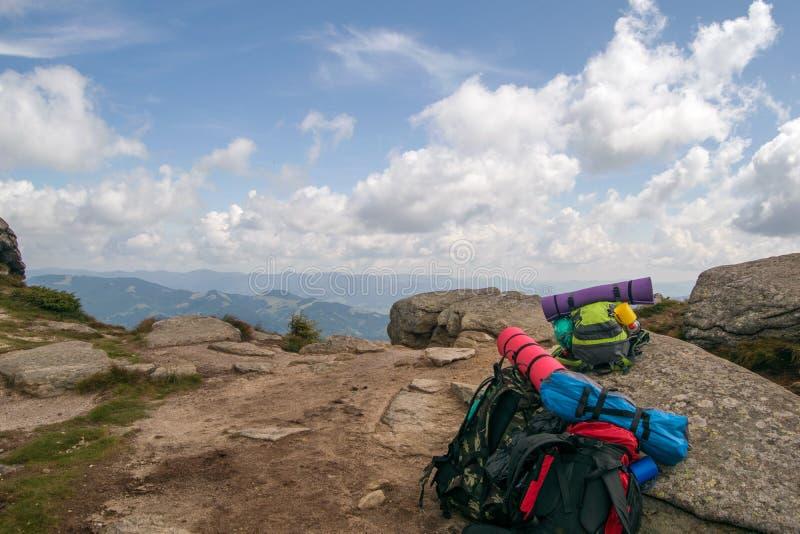 三在山的峰顶的turistic背包 免版税库存图片