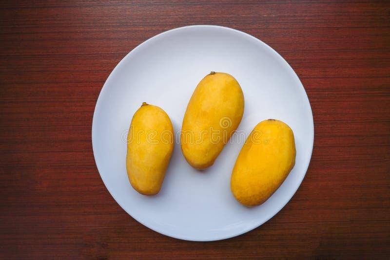 三在板材服务的黄色芒果 免版税库存照片