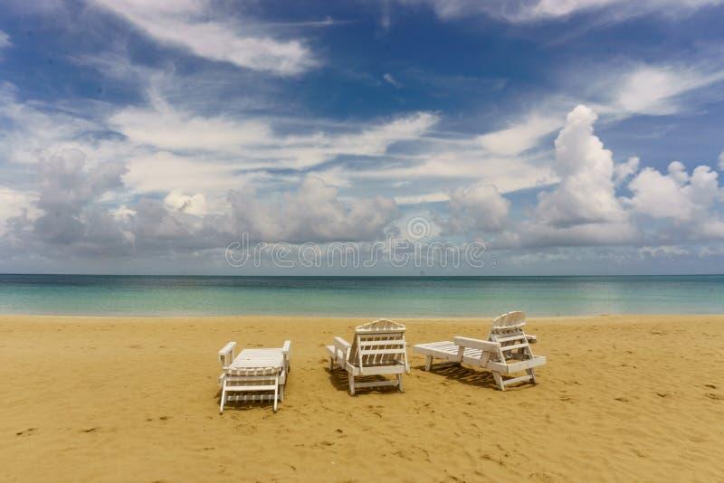 三在海滩的轻便折叠躺椅 图库摄影