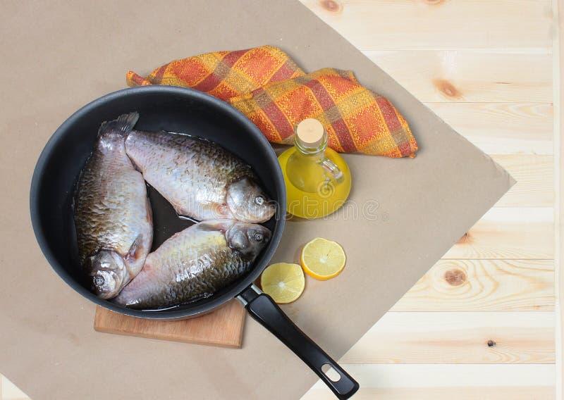 三在煎锅的鲤鱼有在牛皮纸的菜油的 免版税库存照片