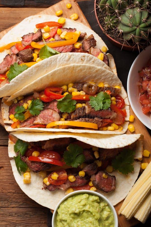 三块墨西哥炸玉米饼用使有大理石花纹的牛肉、黑人安格斯和菜在老土气桌上 与调味汁鳄梨调味酱捣碎的鳄梨酱和婆罗双树的墨西哥盘 图库摄影