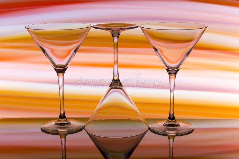 三块鸡尾酒/马蒂尼鸡尾酒玻璃连续与颜色彩虹在他们后 免版税库存照片