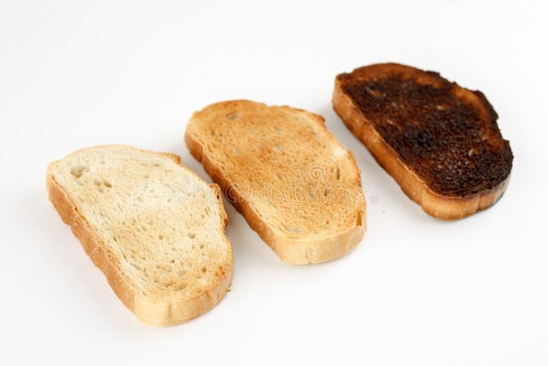 三多士用不同的阶段烤在白色背景 库存图片