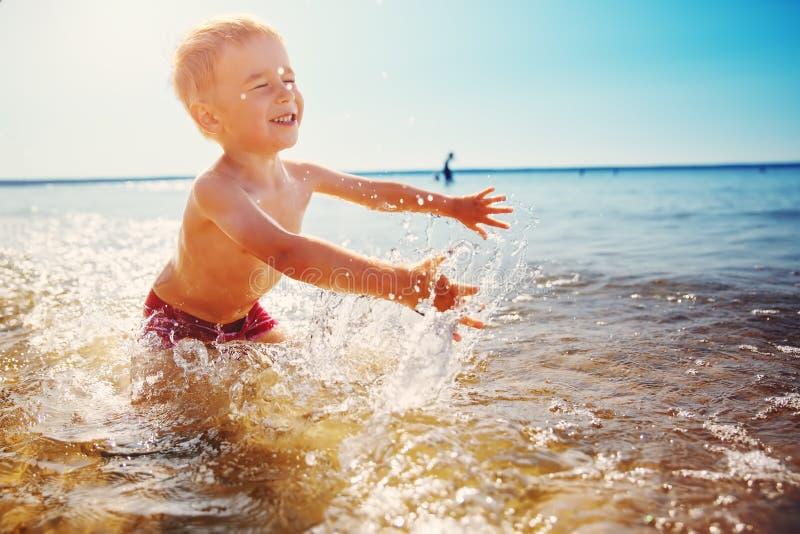 三岁使用在与游泳的圆环的海滩的男孩 图库摄影