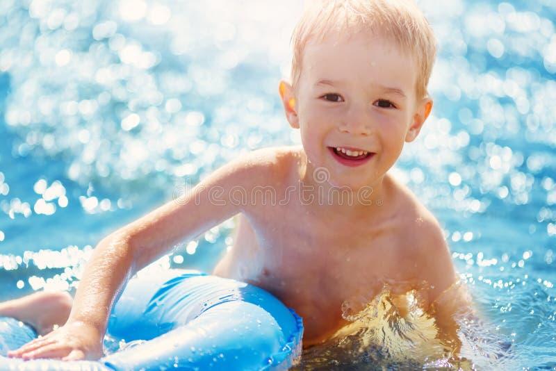 三岁使用在与游泳的圆环的海滩的男孩 免版税图库摄影