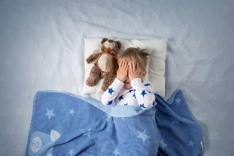 三岁哭泣在床上的儿童 免版税库存照片