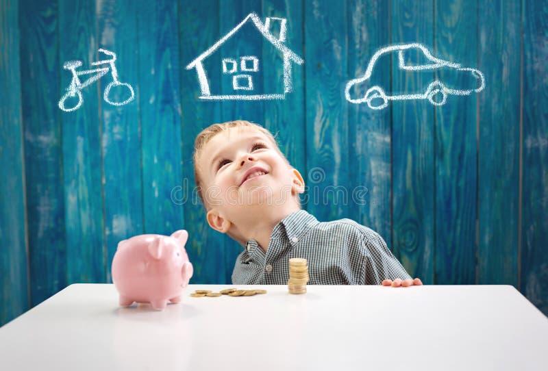 三岁坐st的儿童与金钱和piggybank的桌 免版税库存图片