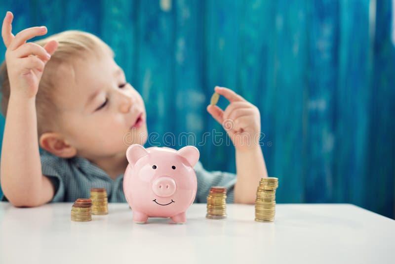 三岁坐st的儿童与金钱和piggybank的桌 库存图片