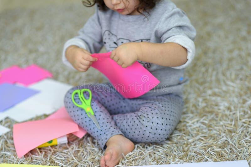 三岁的小孩女孩的关闭删去了与剪刀,与孩子的工艺,裁减,爱好,时间 免版税图库摄影
