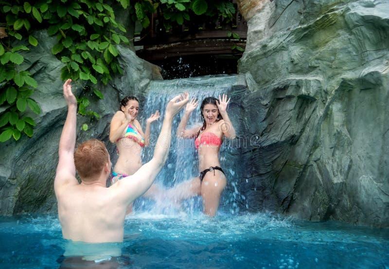 三年轻人获得乐趣用瀑布的落的水在水池 库存图片