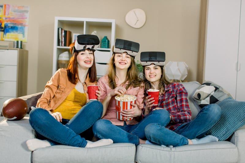 三年轻可爱的妇女佩带的耳机VR虚拟现实视觉风镜,有党在家,吃玉米花 免版税库存图片