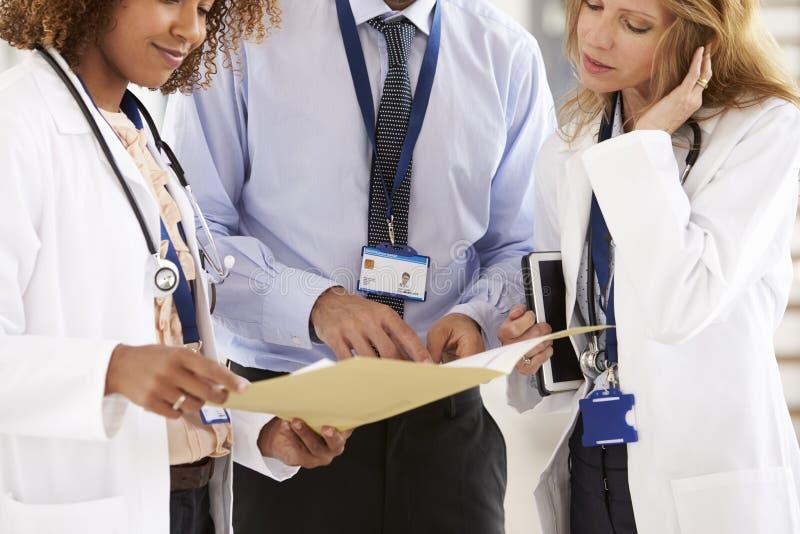 三年轻咨询男性和女性部分的医生,中间 免版税库存照片