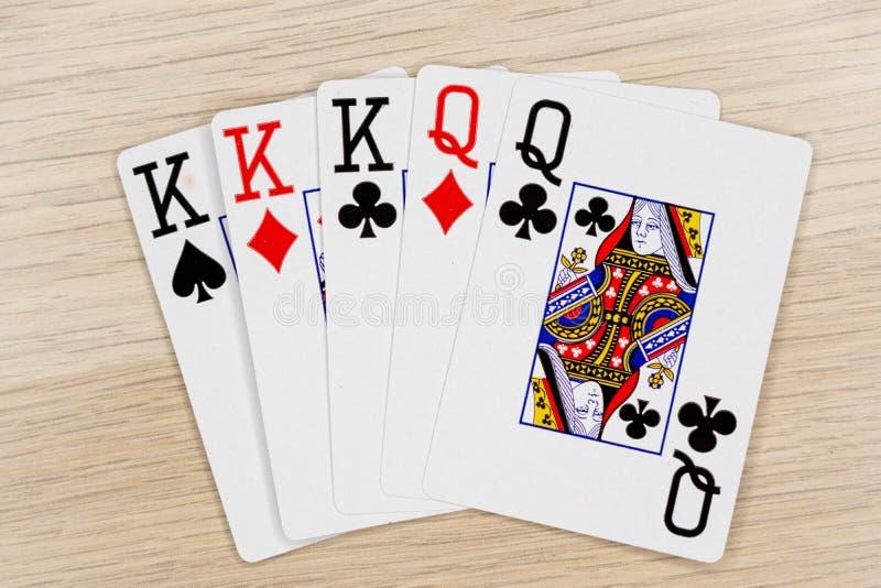 三张相同和二张相同的牌国王女王/王后-打啤牌牌的赌博娱乐场 免版税库存照片