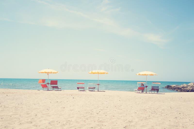 三把伞和椅子在沙滩在阿尔巴尼亚的都拉斯,亚得里亚海岸 库存照片