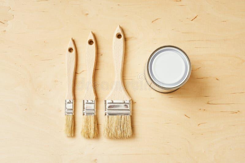 三把刷子和银色油漆在一个木板能 免版税库存照片