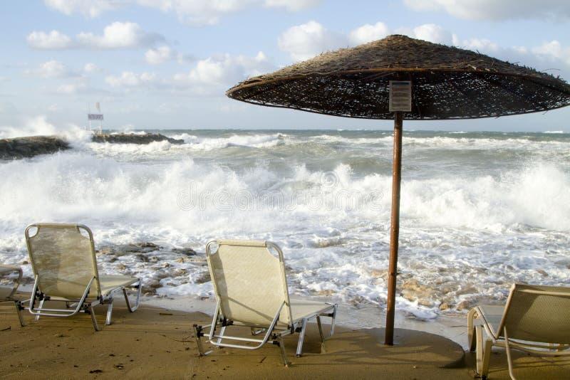 三把椅子和太阳机盖在一个风雨如磐的海滩 免版税库存照片