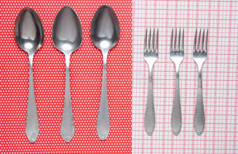 三把金属匙子和叉子在桌布 免版税库存图片