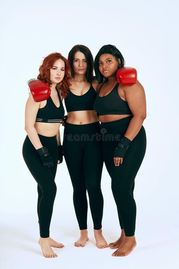 三摆在拳击手套的黑运动服的多种族不同的妇女 库存图片