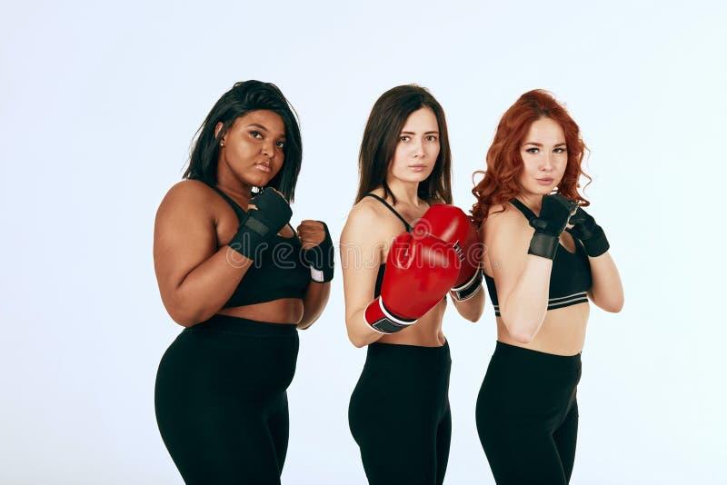 三摆在拳击手套的黑运动服的多种族不同的妇女 免版税库存图片