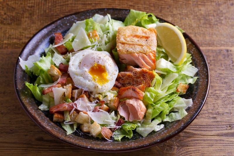 三文鱼凯萨色拉 酥脆平底锅油煎了三文鱼内圆角、烟肉、荷包蛋、莴苣和油煎方型小面包片穿戴用帕尔马干酪 库存照片
