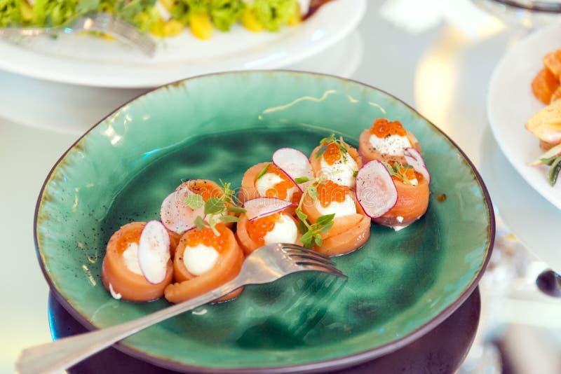 三文鱼卷用软干酪和红色鱼子酱在一块绿色板材 库存图片