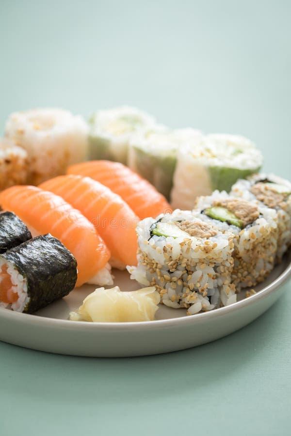 三文鱼和金枪鱼寿司有Nigiri、梅基和里里外外加利福尼亚卷的混合板材 免版税库存照片