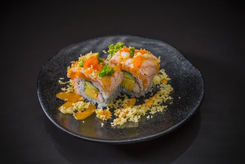 三文鱼寿司卷用辣调味汁和天麸罗 免版税库存照片