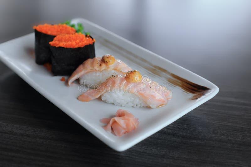 三文鱼烤了nigiri寿司和梅基寿司与飞鱼獐鹿,日本食物 免版税库存照片