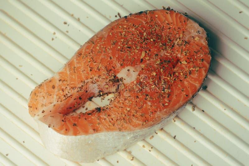 三文鱼照片  新鲜的红色鱼深颜色 三文鱼在电格栅鱼片 在香料,干蓬蒿,盐,胡椒 三文鱼 免版税库存照片