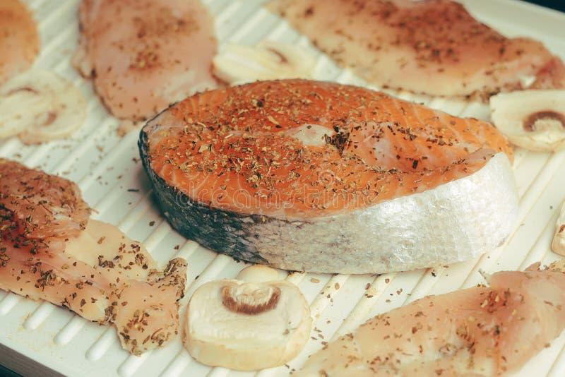 三文鱼照片  新鲜的红色鱼深颜色 蘑菇和鸡内圆角在格栅 在香料,干蓬蒿,盐,胡椒 免版税库存照片